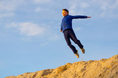 Teenager jumping against the sky. Parkour. On the sand Stock Image
