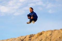 Teenager jumping against the sky. Parkour. On the sand Stock Photos
