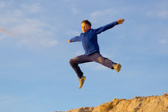 Teenager jumping against the sky. Parkour. On the sand Royalty Free Stock Photos