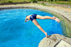 Teenager jumping into pool. Teen dives into a swimming pool with springboard royalty free stock photography