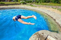 Teenager jumping into pool Royalty Free Stock Image