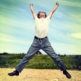 Teenager is Jumping. Toned photo of Happy Teenager Jumping on the Beach Royalty Free Stock Images