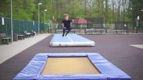 Teenager jumping on a trampoline. Teenager alone jumping on a trampoline in a park stock video footage