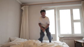 Teenager jumps on the bed stock video footage