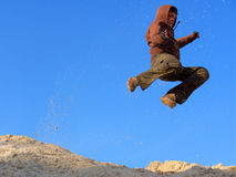 Teenager jumps on sand Royalty Free Stock Image
