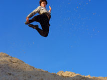 Teenager jumps from sand hill Stock Photo