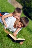 Teenager and kid with a book. The happy teenager and kid with a book on a summer meadow Royalty Free Stock Photo