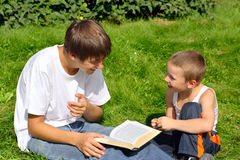 Teenager and kid with a book. The happy teenager and kid with a book on a summer meadow Stock Photos