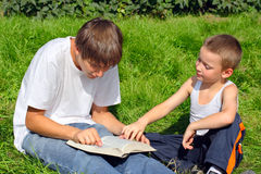 Teenager and kid with a book. On a summer meadow Royalty Free Stock Images