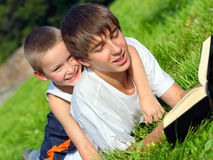 Teenager and kid with a book. The teenager reads the book to the child Royalty Free Stock Image