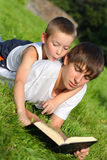 Teenager and kid with a book Stock Images