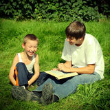 Teenager and Kid with a Book Stock Photos