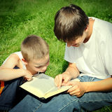 Teenager and Kid with a Book. Vintage photo of The Teenager reads the Book to the Child Stock Photos