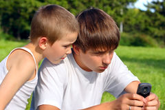 Teenager and kid with mobile phone Stock Photo