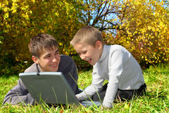 Teenager and kid with notebook Royalty Free Stock Photography