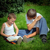 Teenager and Kid read a Book Stock Photo