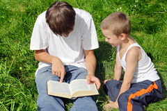 Teenager And Kid Reads Book Stock Photos