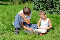 Teenager And Kid Reads Book Stock Photography
