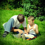 Teenager and Kid reads a Book. Toned photo of Teenager reads the Book to the Child Royalty Free Stock Photo