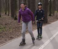 Teenager kids roller skating in the park royalty free stock photos