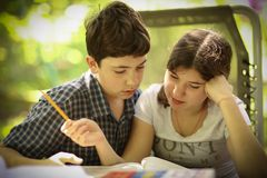 Teenager kids siblings sister help her brother with homework task stock images