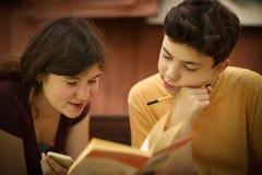 Teenager kids siblings sister help her brother with homework task Stock Photos