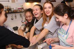 Teenager kids team cooking having fun. Moscow, Russia, November 21, 2017: Unidentified teenager kids cooking pasta on culinary master class - happy event Royalty Free Stock Photography