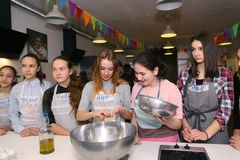 Teenager kids team cooking having fun. Moscow, Russia, November 21, 2017: Unidentified teenager kids cooking pasta on culinary master class - happy event Royalty Free Stock Image