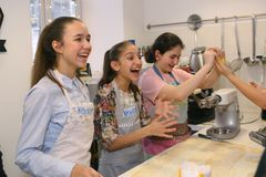 Teenager kids team cooking having fun. Moscow, Russia, November 21, 2017: Unidentified teenager kids cooking pasta on culinary master class - happy event Royalty Free Stock Photo