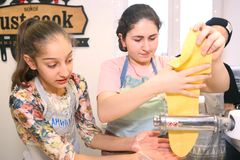 Teenager kids team cooking having fun. Moscow, Russia, November 21, 2017: Unidentified teenager kids cooking pasta on culinary master class - happy event Stock Photography