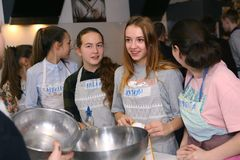 Teenager kids team cooking having fun. Moscow, Russia, November 21, 2017: Unidentified teenager kids cooking pasta on culinary master class - happy event Stock Photo