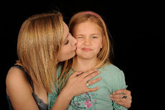 Teenager kissing young sister Stock Images