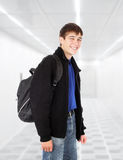 Teenager with knapsack. In the white corridor Stock Image