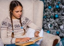 Teenager in a knitted sweater sits in an armchair by the Christmas tree and reads a book. Girl teenager in a knitted sweater sits in an armchair by the Christmas Stock Photos