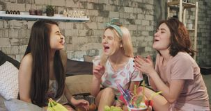 A teenager ladies have a sleepover party at home on pajamas eating chewing gum and make a big bubbles in front of the stock video