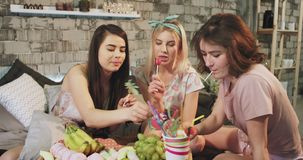 Teenager ladies multi ethnic at home in the bedroom eating lollipops and have a sweets party time in pajamas. stock video footage
