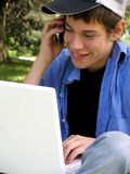 Teenager with a laptop and cellular. Teenager is outside busy with a laptop while using a cellular phone royalty free stock photo