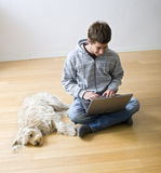 Teenager and laptop computer and dog Stock Image