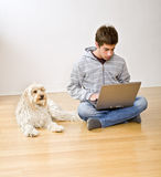 Teenager and laptop computer and dog. Teenager with a laptop computer and his dog on a parquet floor royalty free stock photography