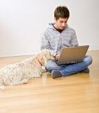Teenager and laptop computer and dog. Teenager with a laptop computer and his dog on a parquet floor stock photos