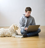 Teenager and laptop computer and dog. Teenager with a laptop computer and his dog on a parquet floor stock photography