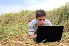 Teenager with a laptop in the field Stock Photo