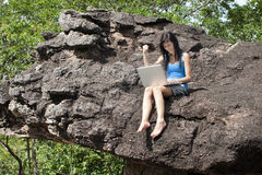 Teenager with laptop sits on rock Stock Photography