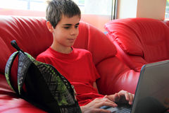 Teenager using a laptop. Teenager sitting in a chair and using a laptop Stock Photos
