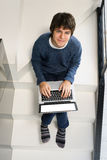 Teenager and latop. Teenager boy sitting on stairs and using laptop, copy space on blank screen Royalty Free Stock Images