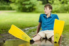 Teenager laying back in puddle Stock Photo
