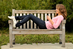 Teenager laying on bench texting Stock Photo