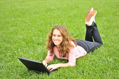 Teenager laying on grass with a laptop Stock Image