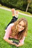 Teenager laying on grass texting Stock Image