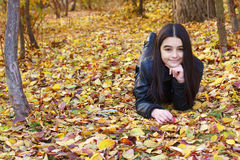Teenager laying on leaves Stock Images